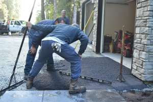 workers grading the slope of the driveway