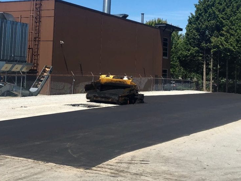 Parking lot paving contractors are installing new asphalt on the parking lot